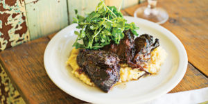 Braised beef cheeks with rutabaga mash and pea shoots.Photography by Scott Suchman