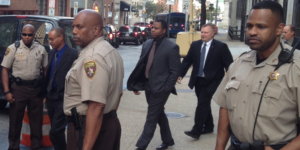 The trial Baltimore police officer William Porter (center, gray suit, black shirt), seen here leaving an earlier motion hearing, starts Monday.Photography by Ron Cassie
