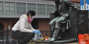 Conservator Kenya Brown at work on restoring the Edgar Allan Poe statue at the University of Baltimore.Courtesy of Jeff Feeser Photography