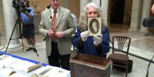Terry Drayman-Weisser, of The Walters Art Museum, pulls a portrait of Francis Scott Key from a 1915 time capsule discovered inside Baltimore's Washington Monument.Photo by Ron Cassie