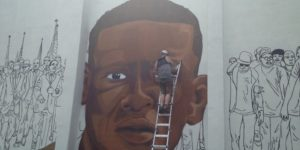 Street artist Nether works on a mural of Freddie Gray at the corner of corner of North Mount and Presbury streets. Photography by Gabriella Souza
