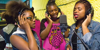 "Left to right: Taniyah, Amira, and Yamaudi record vocals to ""Believe in Baltimore.""Photography by Sean Scheidt"