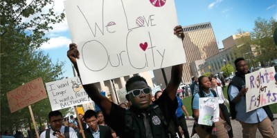 "On April 29, 2015, students from Digital Harbor High School carry homemade signs and chant, ""We love Baltimore"" as they march outside City Hall.Win McNamee/Getty Images"