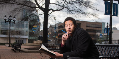 Derick Ebert poses on the University of Baltimore campus with his trusty composition bookPhotography by Mike Morgan