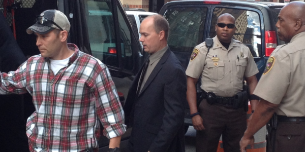 Lt. Brian Rice, center, stepping into a van following a preliminary court hearing last spring.Ron Cassie