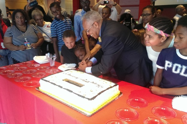 Skipp Sanders cuts the Lewis museum's 10th anniversary cake with young patrons.Courtesy of the Reginald F. Lewis Museum