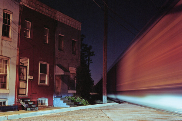 A freight train passes by row homes on the edge of Cherry Hill while the headlights of waiting cars shine through.Photography by Patrick Joust
