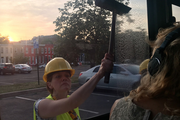 A Single Carrot actor squeegees the bus window during Promenade: Baltimore.Jess Mayhugh