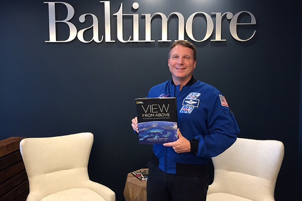 Astronaut Terry Virts holds a copy of his new book, View from Above: An Astronaut Photographs the World.